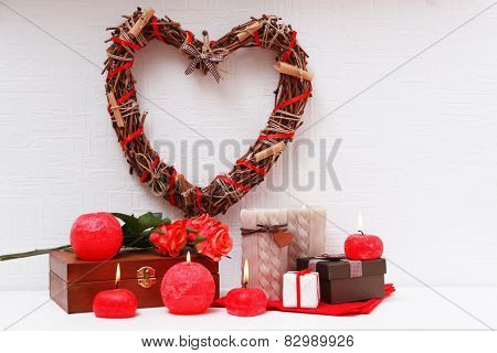 Romantic still life with wicker heart and candle lights on mantelpiece and white wall background