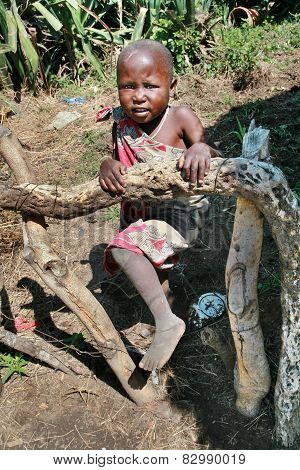 African Child Girl Maasai Tribe, Playing On A Kitchen Garden.