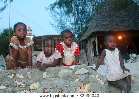 Four Small Black African Girl Resting On A Stone Fence.