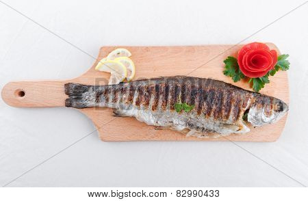 Grilled fish and vegetables on an wooden board