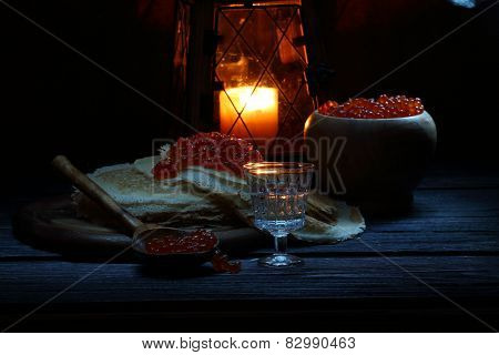 Red caviar on a thin openwork fritter and vodka in a transparent wine-glass