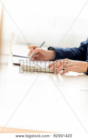 Businesswoman Calculating Sales Using Calculator
