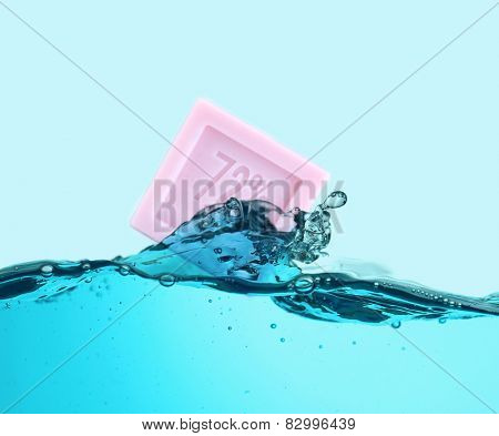 Aromatic pink soap in water splash on blue background
