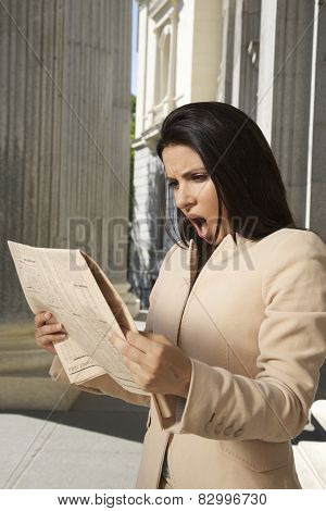 Shocked Businesswoman Reading Newspaper