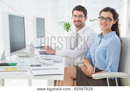 Portrait of smiling team sitting at desk in the office