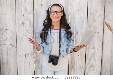 Pretty hipster holding phone and laptop against bleached wooden fence