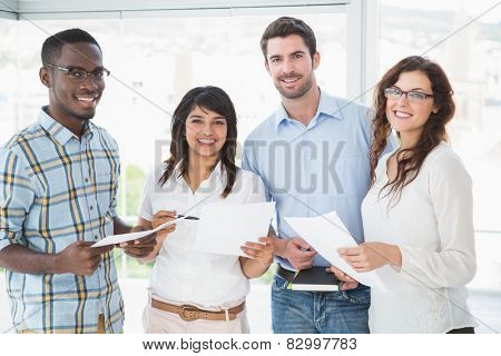 Smiling coworkers holding files and posing in the office