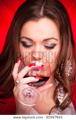 Beautiful young woman drinking red wine - studio shot on red background
