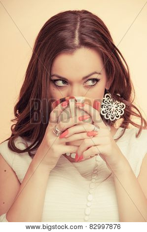 Beautiful young brunette drinking coffee, on beige background
