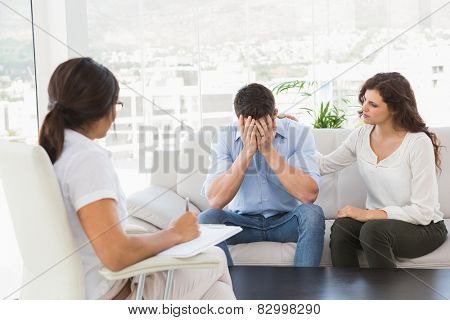 Depressed couple talking with their therapist in the office