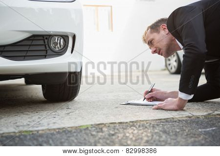 Businessman examining car tire while writing on clipboard in a car park