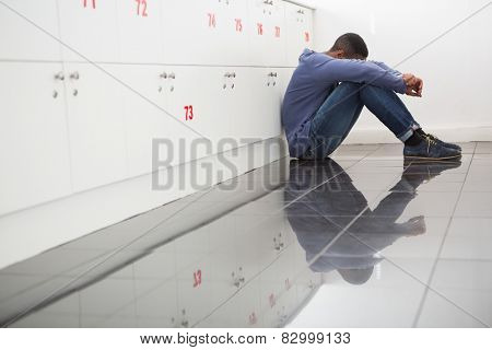 Solitary university student sitting on the floor at the university