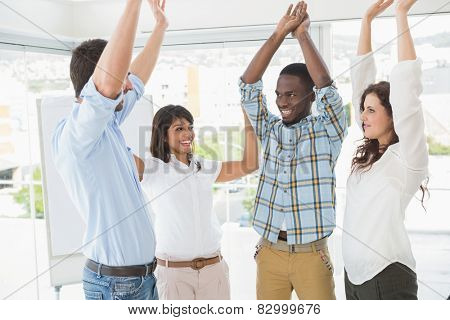 Happy coworkers standing and cheering together in the office