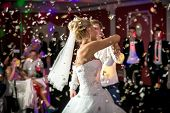 foto of dancing  - Beautiful blonde bride dancing at restaurant in flying confetti - JPG