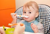 stock photo of child feeding  - Mother feeds the small child baby food - JPG