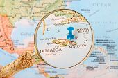 stock photo of caribbean  - Blue tack on map of Caribbean with magnifying glass looking in on Kingston Jamaica - JPG