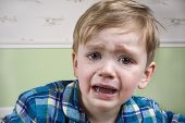 picture of crying boy  - Small boy with big eyes crying dramatically before bedtime - JPG