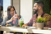 image of lunch  - Cheerful young couple having lunch and healthy smoothies at a juice bar - JPG