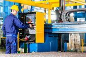 pic of construction machine  - Worker in manufacturing plant at CNC machine control panel - JPG