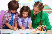 picture of health center  - Teacher, little boy and a girl drawing something in preschool center for children