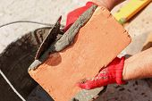 stock photo of bricklayer  - Bricklayer with brick at a construction site