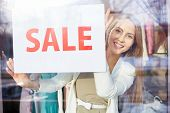 picture of boutique  - Beautiful young woman announcing sale in boutique - JPG