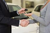 stock photo of showrooms  - Businessman giving car key while shaking a customer hand at new car showroom - JPG