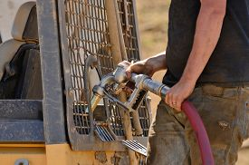 stock photo of bulldozers  - Equipment operator filling up the fuel tank of a small bulldozer with diesel fuel - JPG