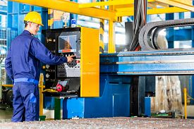 image of southeast  - Worker in manufacturing plant at CNC machine control panel - JPG