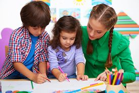 picture of cognitive  - Teacher, little boy and a girl drawing something in preschool center for children ** Note: Shallow depth of field - JPG