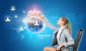 pic of globe  - Businesswoman pressing touch screen button on virtual interface featuring Globe with buildings on top and network with person icons - JPG