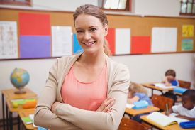 foto of teachers  - Pretty teacher smiling at camera with arms crossed at the elementary school - JPG