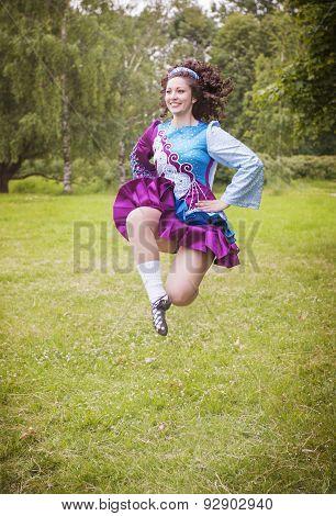 Young Beautiful Girl In Irish Dance Dress Jumping Outdoor