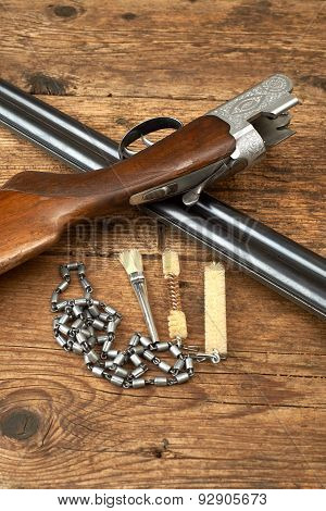 Hunting Gun With Cleaning Kit On A Wooden Table