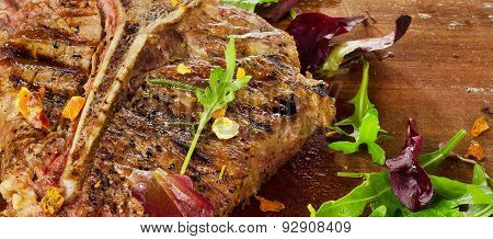 Steak With Fresh Herbs On  Rustic Wooden Table