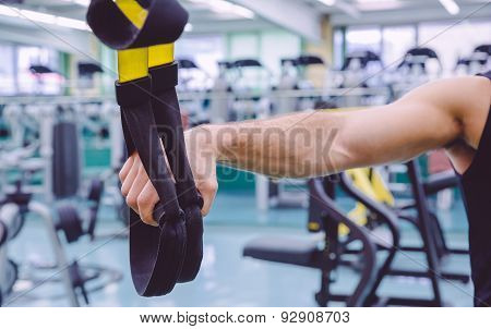 Fitness straps in the hand of man training