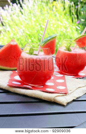 Watermelon drinks with a straw and fresh mint.