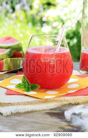 Watermelon drinks outside in the garden with straws and fresh mint. Also available in horizontal.