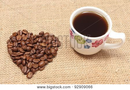 Heart Shaped Coffee Beans And Cup Of Black Coffee