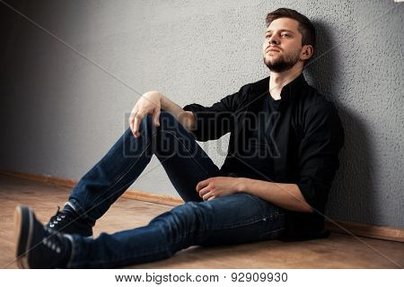 Young Man In Shirt Siting With Hands Clasped Against A Wall