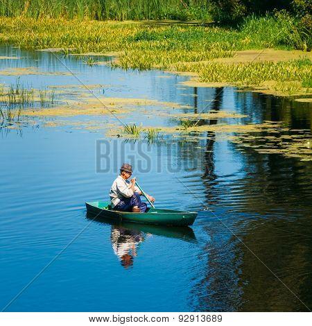 Elderly Man Fishing On River Boat