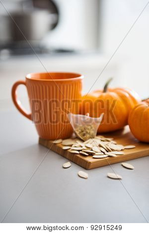 Pumpkin-coloured Mug With Miniature Pumpkins And Seeds On Board