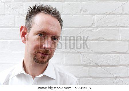 White Shirt Man With White Brick Wall