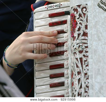 Hand Of A Woman Plays The Ancient Accordion Keyboard