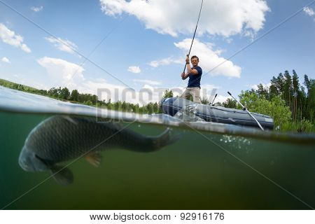 Young man fishing from the boat in the pond. Underwater split shot with fish on the foreground (fish is out of focus)
