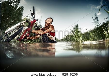Young man athlete with dirty stained clothes pulling his bicycle from the swamp