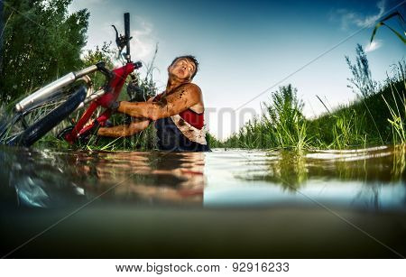 Young man athlete with dirty stained clothes crossing the swamp with bicycle
