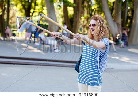 Woman With Curly Hair Pull Soap Bubbles