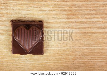 Chocolate heart on wooden texture