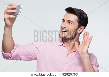 Happy businessman showing greeting sign on smartphone over gray background